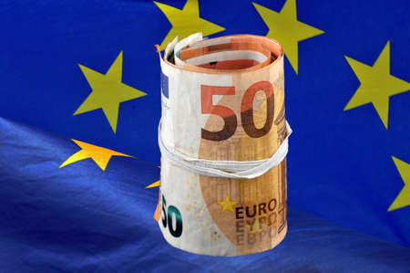 Roll of Euro banknotes on European flag background