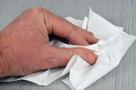 Paper towel in hand for cleaning a wooden surface Standard-Bild