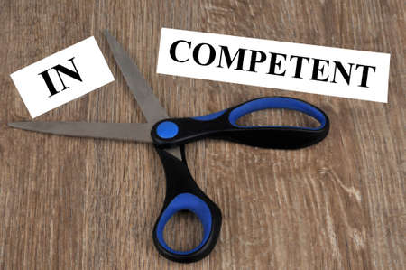 Competence and incompetence concept with a word cut out with scissors