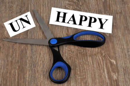 Concept of unhappy and happy with a word cut out with scissors