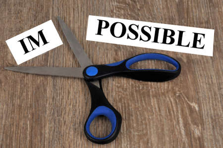 Concept of possibility and impossibility with a word cut out with scissors Standard-Bild