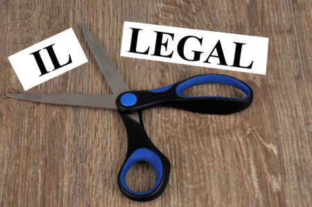 Concept of legality and illegality with a word cut out with scissors