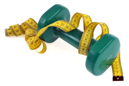 Sport and health concept with a dumbbell and a flexible meter close-up on white background