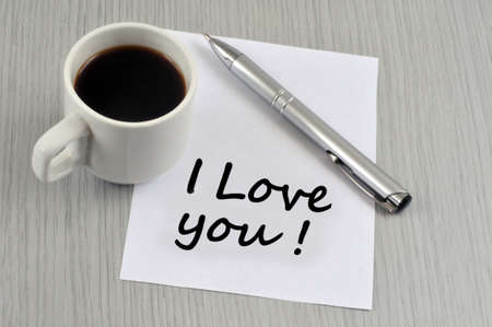 I love you written on a piece of paper next to a cup of coffee