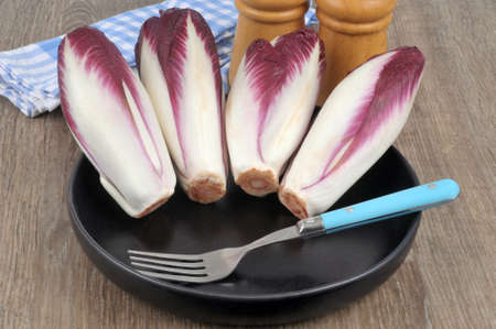 Two-colored endives in a black plate with a fork close-up