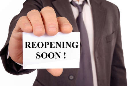 Man holding a card that says reopening soon Stock Photo