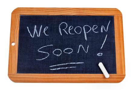 We reopen soon written on a school slate