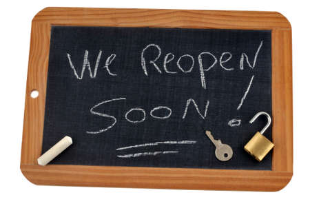 We reopen soon written on a school slate with chalk and an open padlock