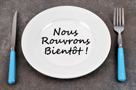 Plate on a gray background in which is written in french we reopen soon