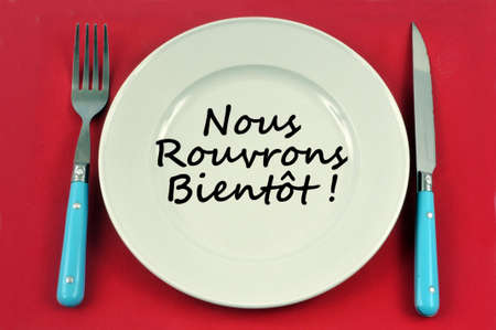 Plate on a gray red ground in which is written in french we reopen soon =