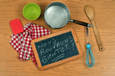 Concept of reopening restaurants with a school slate and kitchen utensils