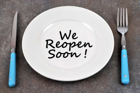 Plate on a gray background in which is written we reopen soon