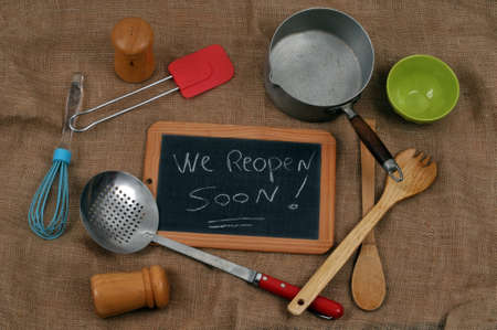 Concept of reopening restaurants with a school slate and kitchen utensils on a burlap