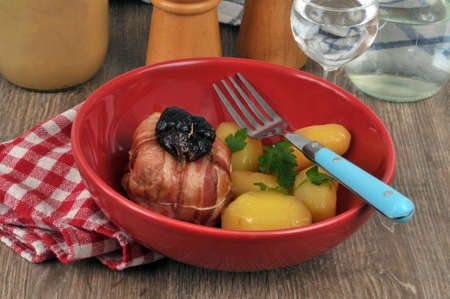 Rabbit paupiette with prunes with potatoes served on a plate