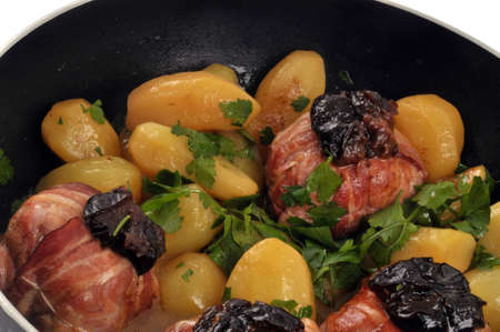 Rabbit paupiettes with prunes with potatoes in a pan close-up
