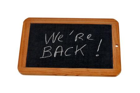 We're back written on a school slate Stock Photo