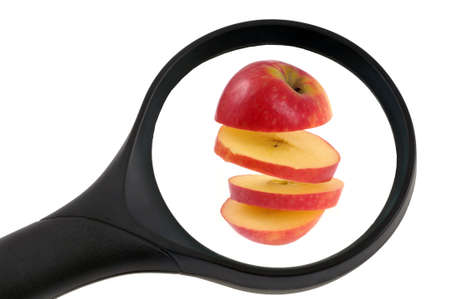 Examination of a sliced apple with a magnifying glass close-up on a white background