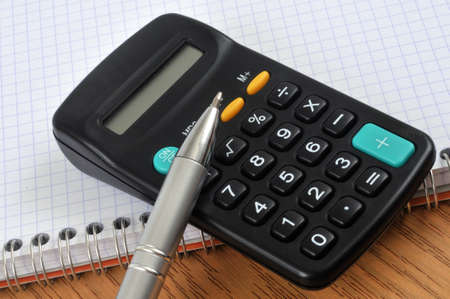 Pen and calculator on a notebook Stock Photo