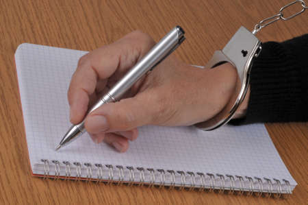 Confession concept with someone handcuffed writing on a spiral notebook with a pen