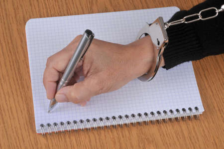 Press freedom concept with someone in handcuffs writing on a spiral notebook with a pen