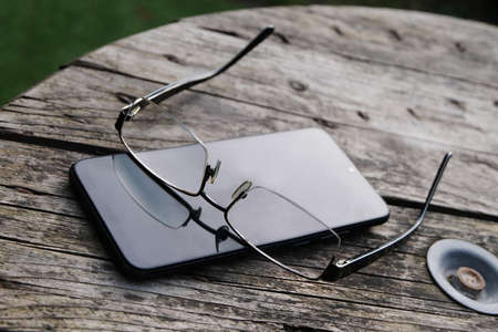 Smartphone and glasses lying on a wooden table