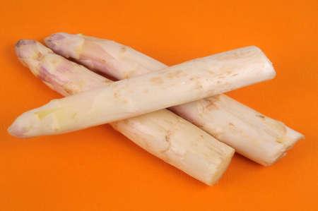 Raw asparagus close up on orange background