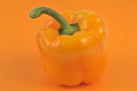 Raw bell pepper close-up on orange background