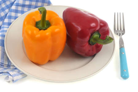 Yellow bell pepper and red bell pepper in a plate with a fork and a checkered napkin close-up on a white background