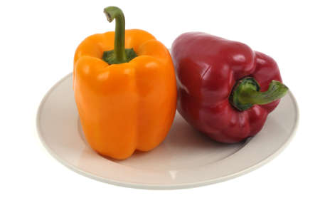 Yellow bell pepper and red bell pepper in a plate close-up on white background