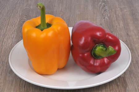 Yellow bell pepper and red bell pepper in a plate close-up