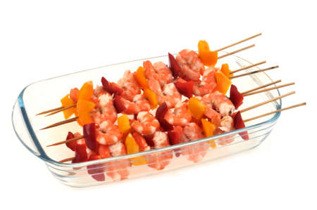 Skewers of shrimp and peppers in a dish close-up on a white background
