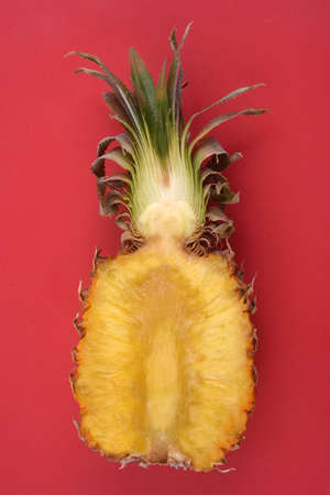 Pineapple cut in half close-up on red background