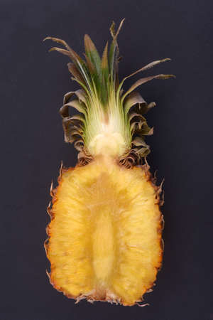 Pineapple cut in half close-up on black background