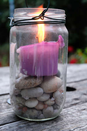 Homemade candle holder with a glass jar, pebbles and a candle