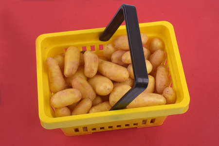 Basket of potatoes close-up on red background Banque d'images