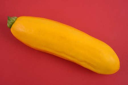 Raw yellow zucchini red background