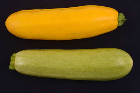 White Lorea zucchini and raw yellow zucchini on black background Banque d'images