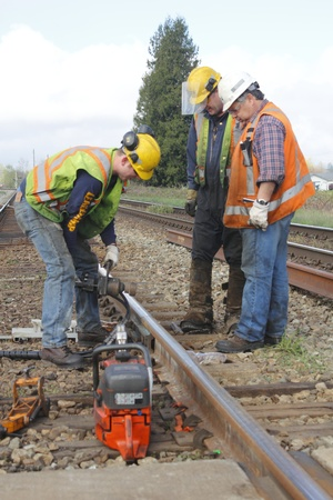 Crew Preforms Railway Track Maintenance