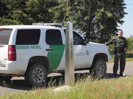 Een US Border Patrol Officer en de door de VS-Canadese grens Marker