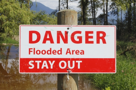 A sign warns to stay away from a flooded area photo