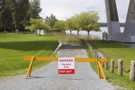 barrier: A barrier warns of a flooded area ahead.