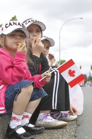 A group of Canadian children sit on the curb to watch a Canada Day parade on July 1st, 2012.  Editorial