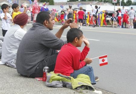 Drie generaties van een Oost-Indische Canadese familie kijken naar de Dag van Canada parade in Abbotsford, British Columbia op 1 juli 2012. Redactioneel