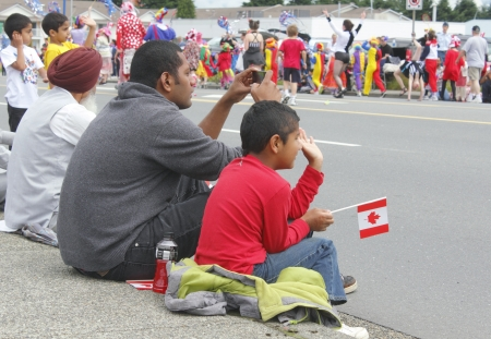 multi generational: Three generations of an East Indian Canadian family watch the Canada Day parade in Abbotsford, British Columbia on July 1st, 2012.