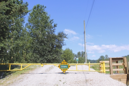 A barrier warns motorists that only emergency vehicles are allowed on the dike