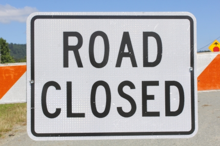 A sign warns that the road up ahead is closed  photo