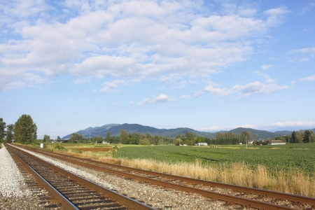 a rural community: Straight and narrow railway tracks cut across a rural community  Stock Photo