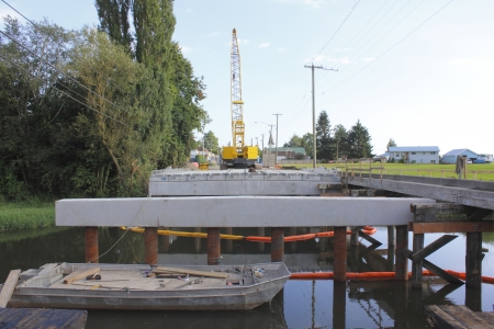 A bridge deck is being assembled for a small bridge spanning a creek in a rural area  photo