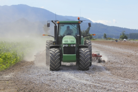 A farmer spreads lime on his field to  sweeten  the soil Stock Photo - 14696091