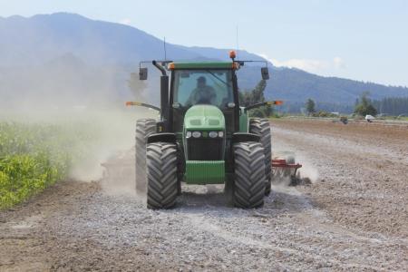 Een boer spreidt kalk op zijn veld te zoeten de bodem